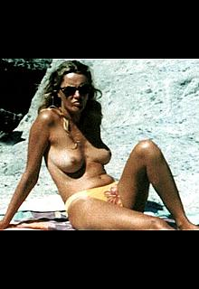Licia Colo sunbathing topless on a beach