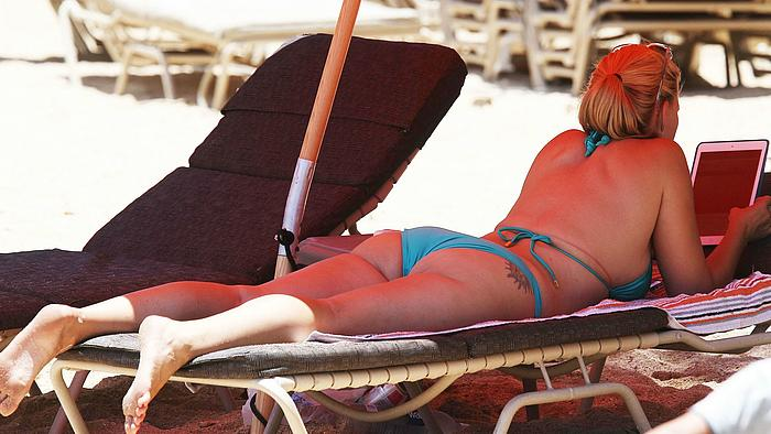 Natasha Henstridge sunbathing in blue bikini on a beach