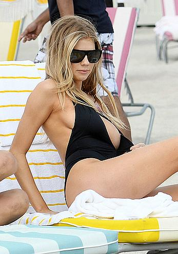 Busty Charlotte McKinney nipple slip in black swimsuit on a beach