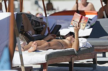 Lucy Aragon sunbathing topless on a beach