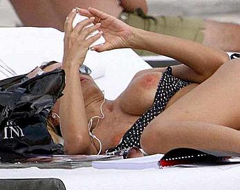 Rita Rusic sunbathing almost topless shows her nude boobs