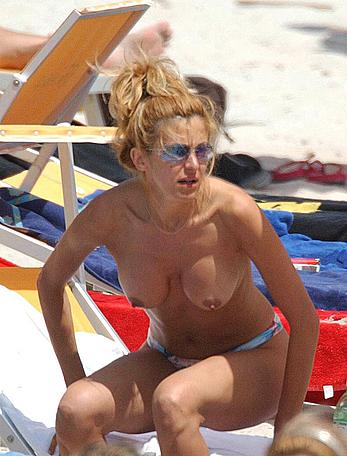Adriana Volpe sunbathint topless on a beach