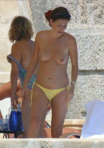 Anna Friel topless in yellow pants on a beach