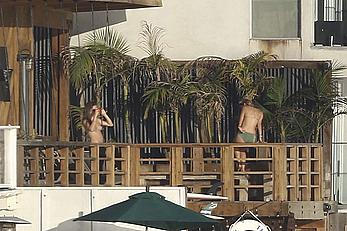 Cara Delevingne sunbathing topless on a balcony in Malibu