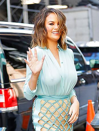 Chrissy Teigen walks out in a see through blouse