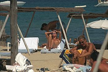 Elle Macpherson sunbathing topless on a beach