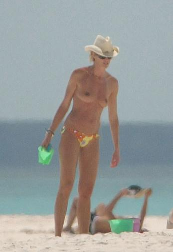 Elle Macpherson topless on a beach