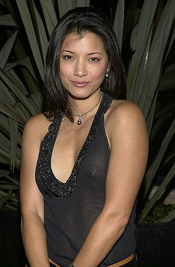 Kelly Hu posing in see through top