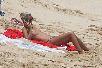 Laeticia Hallyday tanning topless on a beach
