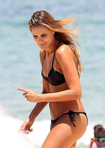 Laura Dundovic in black bikini on Bondi beach