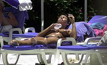 British Lucinda Rhodes-Flaherty sunbathing topless poolside