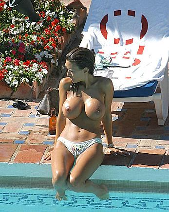Busty Lucy Becker topless poolside in Spain