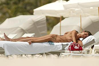 Italian actress Manuela Arcuri sunbathing topless on a beach