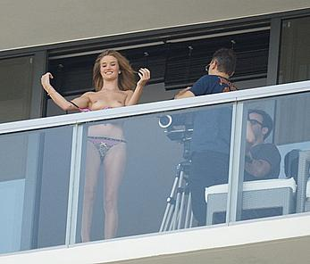 Rosie Huntington-Whiteley topless on a balcony during photoshoot